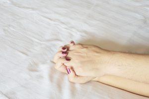 mão de homem segurando a mão de uma mulher na cama relacionado ao desejo sexual e exercício físico.