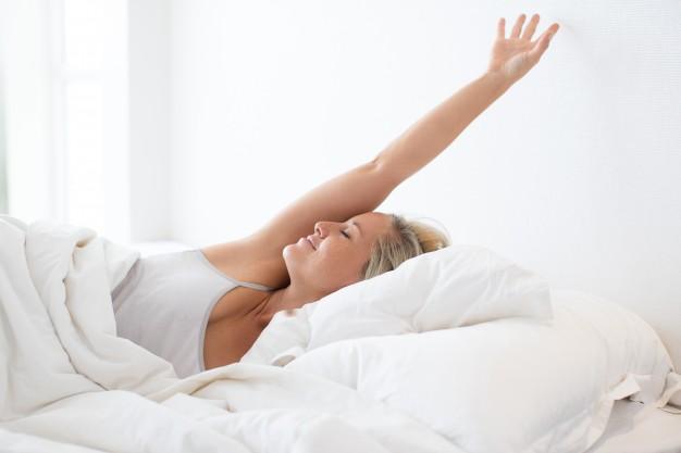 mulher se espreguiçando na cama porque praticou pilates para melhorara a qualidade do sono.
