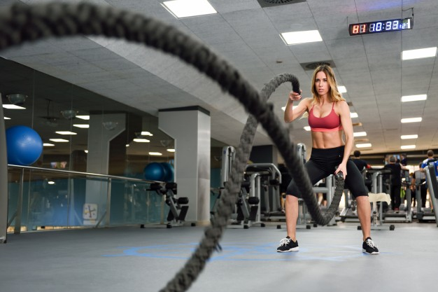 mulher praticando exercício funcional com cordas