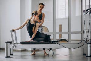 Mulher realizando movimento de pilates sendo observada pela instrutora