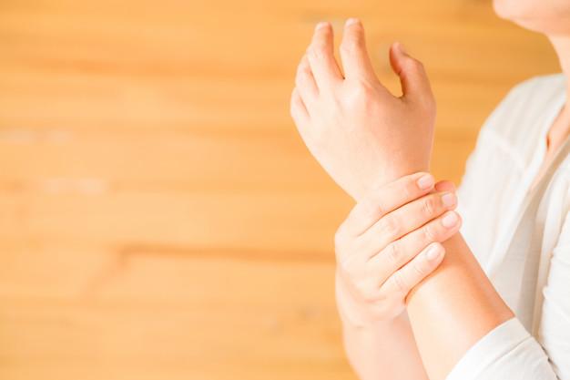 mulher segurando a mão com patologia relacionada ao excesso de whatsapp