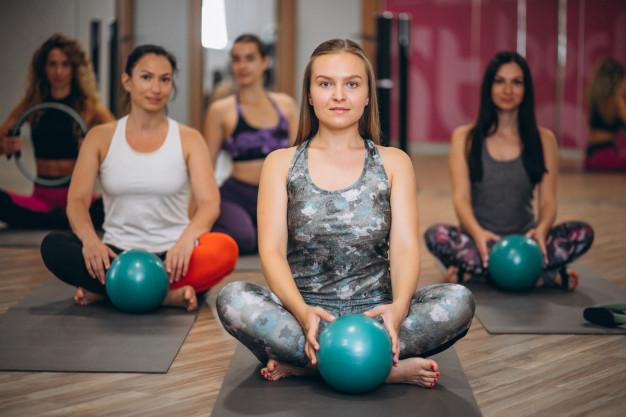 Mulheres na aula de pilates com overball