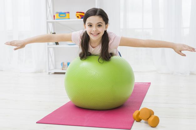 menina com bola realizando exercício de pilates para crianças