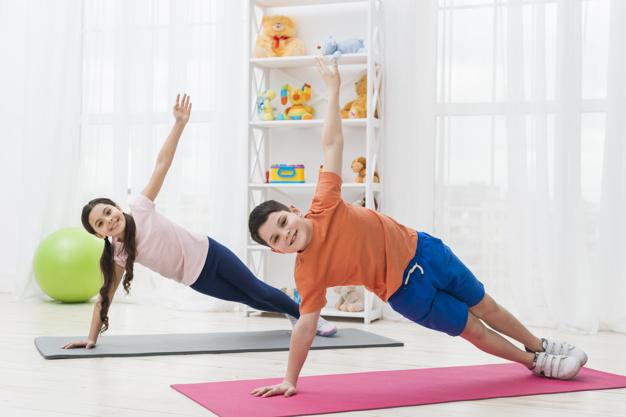 menina e menino realizando exercício de pilates para crianças em colchonete