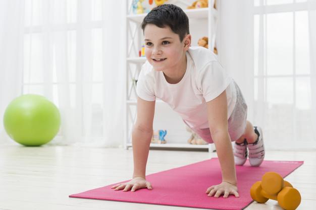 menina na colchonete realizando exercício de pilates para crianças