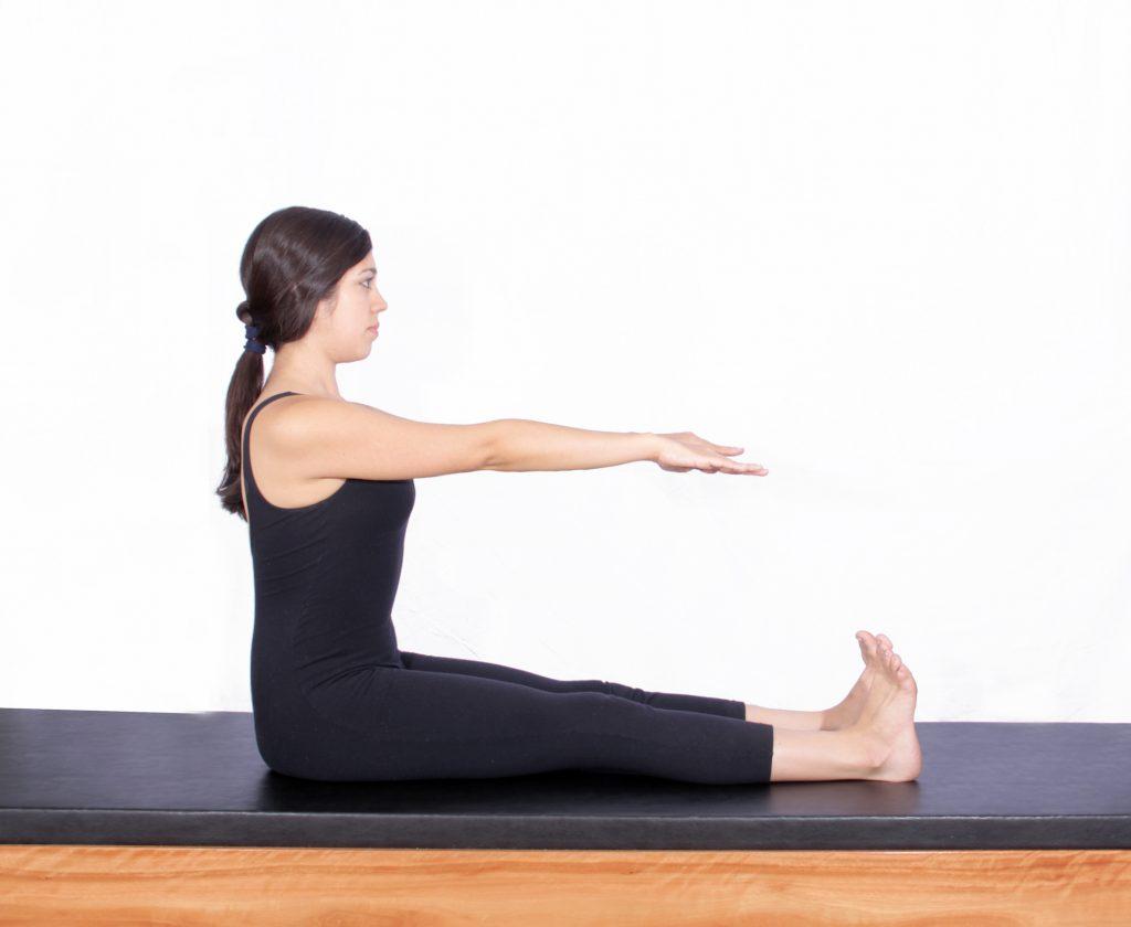 mulher realizando exercício spine stretch de pilates para diabetes