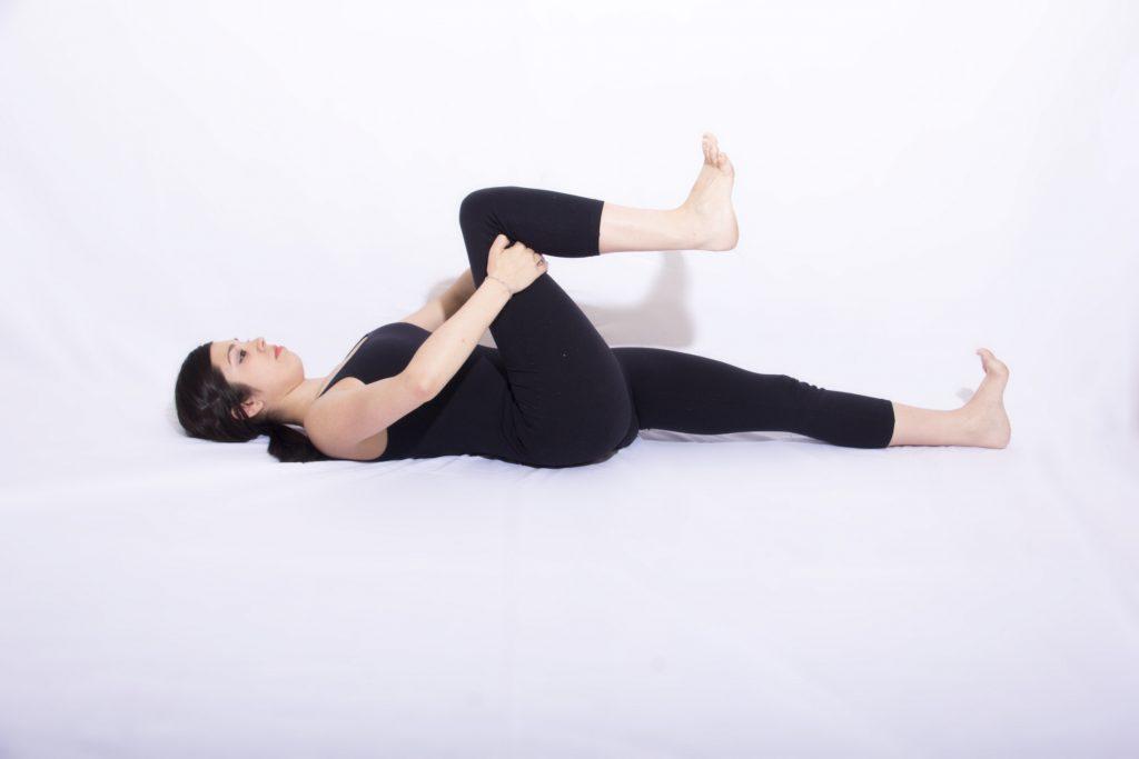 mulher deitada abraçando uma perna