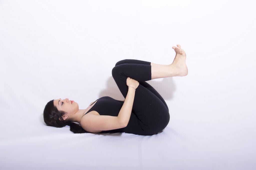 mulher deitada abraçando as duas pernas