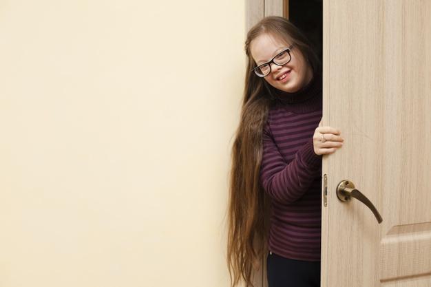 criança com sindrome de down atrás da porta