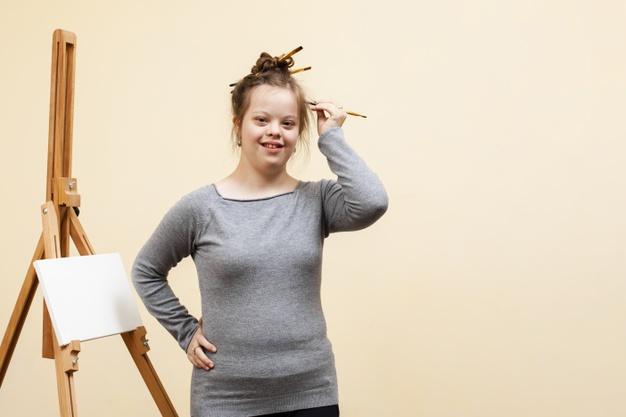 criança com sindrome de down com lápis na cabeça