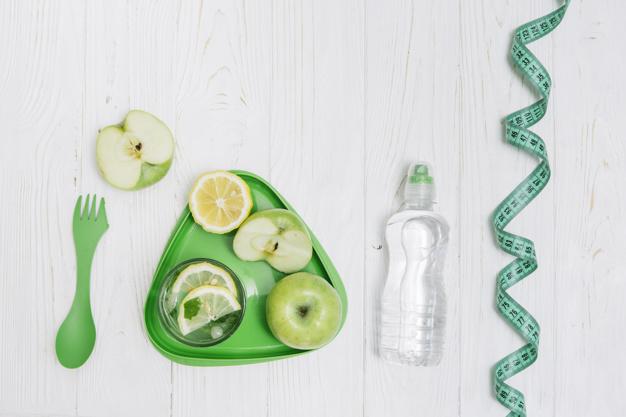 prato de maçã, agua e garfo para representar uma dieta