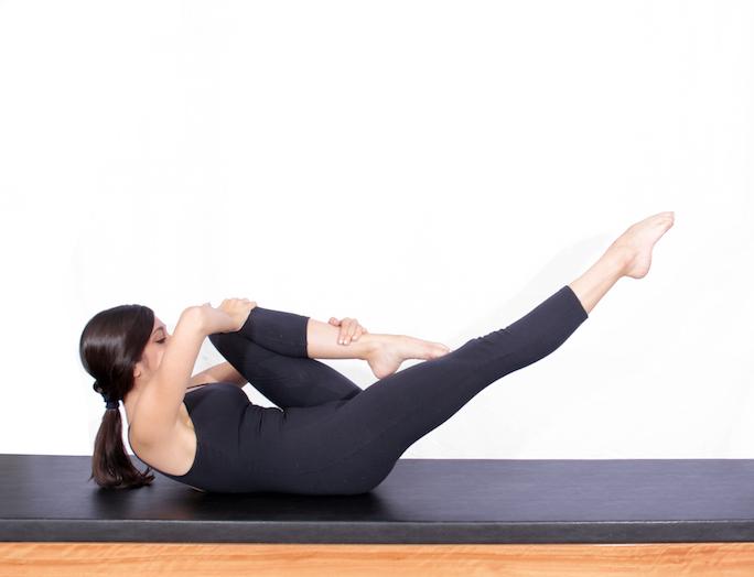 mulher realizando exercício one leg stretch de pilates para diabetes