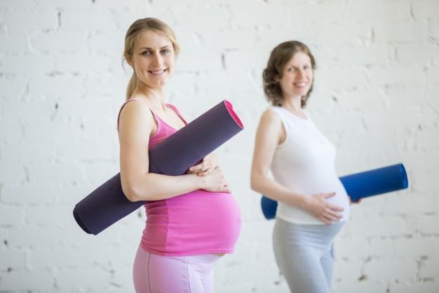 Mulheres grávidas com colchonete de pilates embaixo dos braços