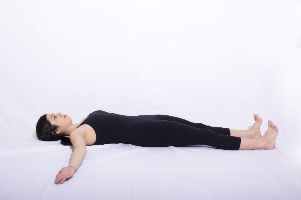 mulher deitada no chão realizando exercicio de respiração