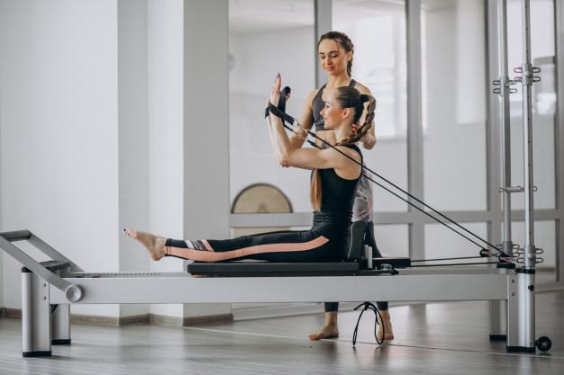 professora realizando exercicio rowing 2 de pilates para aluna