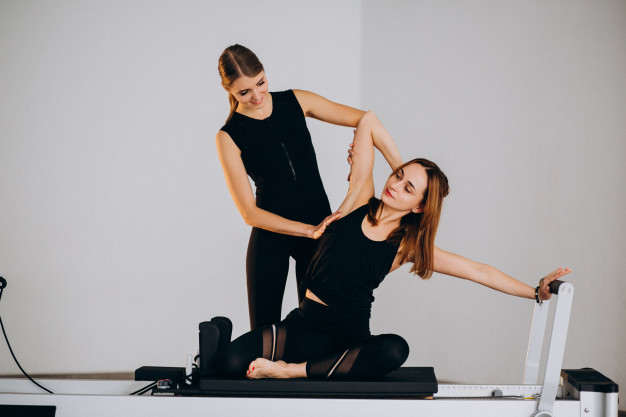 professora realizando exercicio de pilates para aluna