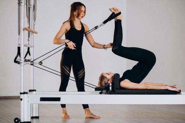 professora realizando exercicio de pilates para aluna em reformer