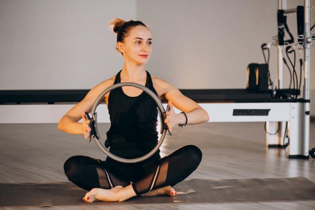 Mulher realizando pilates com magic circle