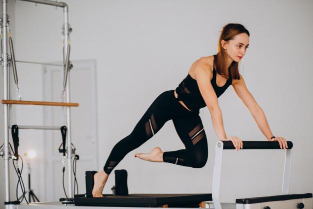 Mulher realizando exercício de pilates no Reformer