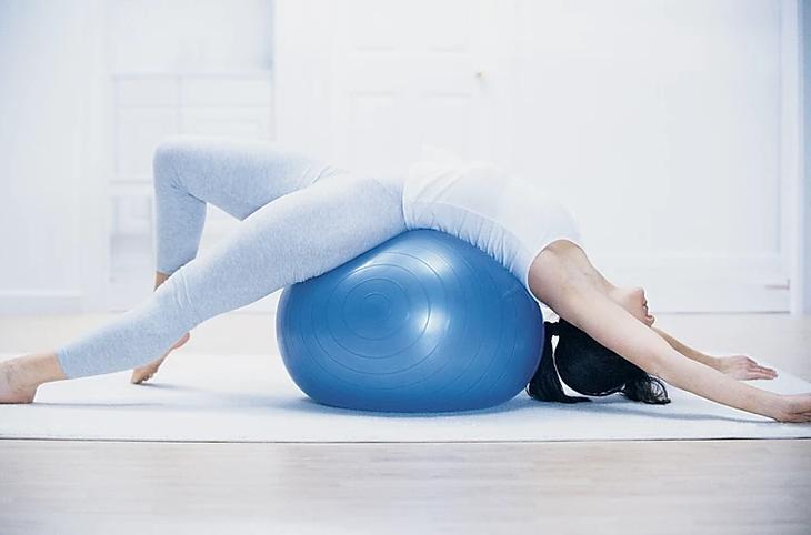 mulher deitada em fitball de pilates