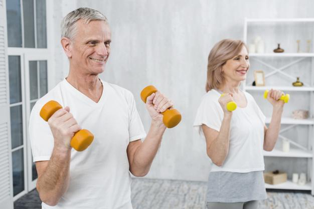 Homem e mulher de terceira idade com halteres nas mãos para prevenir sarcopenia
