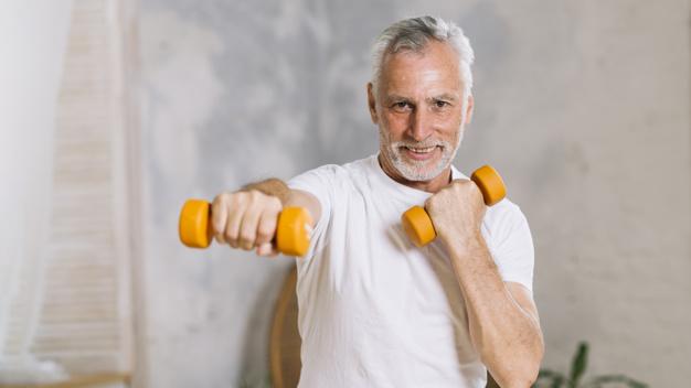 homem de terceira idade realizando exercício punch de pilates com halteres nas mãos
