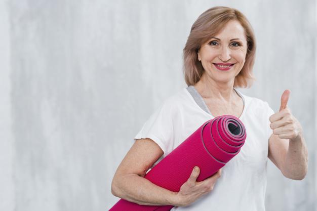mulher de terceira idade com colchonete vermelha de pilates, realizando simbolo de ok com as mãos
